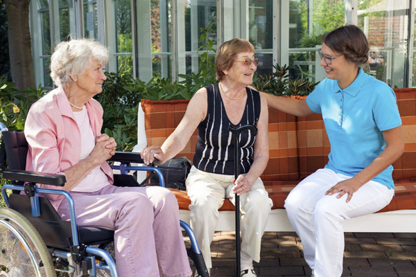 Two old women sitting chatting on a garden bench supported by a carer.